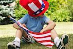 Boy Wearing Large Stars and Stripes Hat, Holding American Flag, Sitting on Grass    Stock Photo - Premium Royalty-Free, Artist: Masterfile, Code: 600-01042023