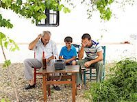 Grandfather, Father and Son Watching Television in Backyard    Stock Photo - Premium Royalty-Freenull, Code: 600-01043375