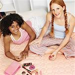 elevated view two teenage girlfriends (16-18) at a sleepover painting nails