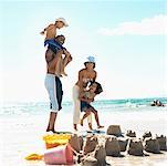 father giving son (8-9) piggyback on shoulders and mother lifting daughter (6-7) at beach