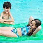 boy (8-9) standing in swimming- pool and girl (8-9) lying on lilo