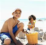 close up of brother (8-9) and sister (6-7) making sandcastles at beach