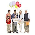 Portrait of a three generation family holding balloons and gifts and a birthday cake Stock Photo - Premium Royalty-Free, Artist: Raoul Minsart, Code: 627-01063236