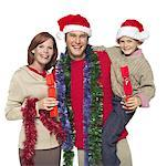 Portrait of parents and son (8-9) holding tinsel and Christmas crackers Stock Photo - Premium Royalty-Free, Artist: Marie Blum, Code: 627-01066967