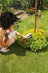 Woman Inspecting Flowers With Magnifying Glass
