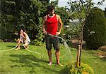 Couple in Garden, Woman Pinching Hose