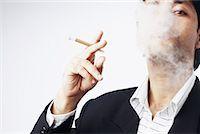 Portrait of a businessman smoking a cigar Stock Photo - Premium Royalty-Freenull, Code: 630-01078366