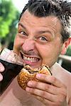Man Eating Hamburger    Stock Photo - Premium Rights-Managed, Artist: Siephoto, Code: 700-01083231