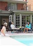 Women Lounging By Pool