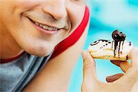 Close-up of a young man holding an eclair and smiling Stock Photo - Premium Royalty-Freenull, Code: 625-01093561