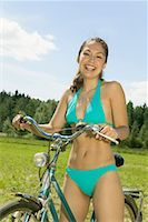 Young woman in bikini with bicycle, portrait Stock Photo - Premium Royalty-Freenull, Code: 613-01103338