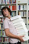 Young man carrying pile of books, looking over shoulder Stock Photo - Premium Royalty-Free, Artist: Blend Images, Code: 613-01103823