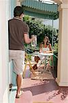 Man going inside home, woman sitting at table on porch Stock Photo - Premium Royalty-Free, Artist: Masterfile, Code: 613-01104410