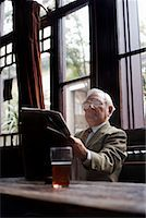 Man Reading Newspaper in Pub    Stock Photo - Premium Royalty-Freenull, Code: 600-01123738