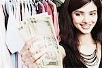 Close-up of a young woman holding banknotes in a clothing store Stock Photo - Premium Royalty-Freenull, Code: 630-01128000