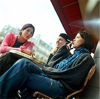 Three teenage girls sitting at cafe terrace, smoking cigarettes, low angle view Stock Photo - Premium Royalty-Freenull, Code: 632-01137069