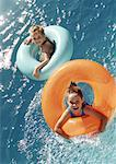Two little girls floating in inflatable rings in water, high angle view Stock Photo - Premium Royalty-Freenull, Code: 632-01141696