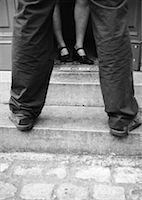 Woman in doorway, man on steps, low section, b&w Stock Photo - Premium Royalty-Freenull, Code: 632-01147285