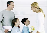 Man with boy and girl facing woman with gifts and flowers Stock Photo - Premium Royalty-Freenull, Code: 632-01151571