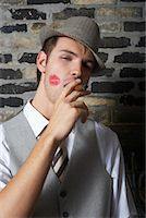 Portrait of Man With Lipstick Mark on Cheek, Smoking a Cigar    Stock Photo - Premium Royalty-Freenull, Code: 600-01163447