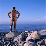 Naked Man Standing on Beach