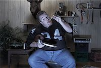fat man balls - Man Watching Football Game on Television and Eating Pizza    Stock Photo - Premium Royalty-Freenull, Code: 600-01163907
