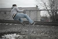 running away scared - Man Climbing over Fence    Stock Photo - Premium Royalty-Freenull, Code: 600-01184409