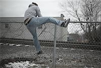 running away scared - Man Climbing over Fence    Stock Photo - Premium Royalty-Freenull, Code: 600-01184410