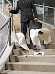 Businessman Dropping Papers on Staircase