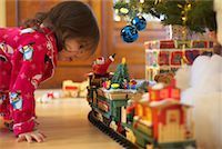 Little Girl Looking at Toy Train    Stock Photo - Premium Royalty-Freenull, Code: 600-01195006