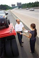 Woman paying tow truck driver Stock Photo - Premium Royalty-Freenull, Code: 604-01231578