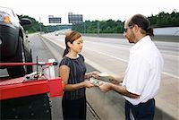 Woman paying tow truck driver Stock Photo - Premium Royalty-Freenull, Code: 604-01232255