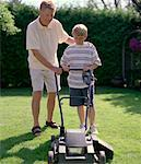 Father Teaching Son to Mow Lawn
