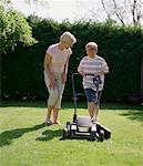 Mother Teaching Son to Mow Lawn