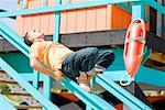 Mid adult man lying on the hand rail of a lifeguard hut Stock Photo - Premium Royalty-Free, Artist: Arian Camilleri          , Code: 625-01250753