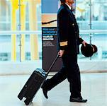Side profile of a pilot pulling luggage at an airport, Madrid, Spain Stock Photo - Premium Royalty-Free, Artist: Michael Mahovlich, Code: 625-01251184