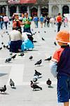 Rear view of a boy standing and looking at pigeons, Venice, Veneto, Italy Stock Photo - Premium Royalty-Free, Artist: IIC, Code: 625-01252285