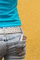 Close-up of a mobile phone in a teenage girl's back pocket Stock Photo - Premium Royalty-Freenull, Code: 625-01261781