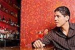 Close-up of a young man sitting at a bar counter and holding a cocktail Stock Photo - Premium Royalty-Free, Artist: Glowimages, Code: 625-01262392