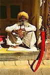 Portrait of a senior man sitting at a veranda of a museum, Meherangarh Museum, Jodhpur, Rajasthan, India