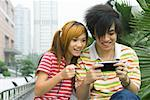 Teenage couple playing with handheld video game, outdoors Stock Photo - Premium Royalty-Free, Artist: Cusp and Flirt, Code: 632-01271113