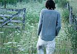 Man walking in field, rear view