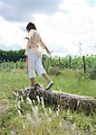 Girl walking on log, arms out