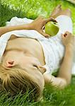 Young woman lying in grass, holding apple Stock Photo - Premium Royalty-Free, Artist: Raimund Linke            , Code: 633-01274933