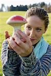 Young woman holding an artificial fly agaric, selective focus Stock Photo - Premium Royalty-Free, Artist: Visuals Unlimited, Code: 628-01279676