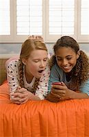 Preteen girls reacting to text message Stock Photo - Premium Royalty-Freenull, Code: 621-01305633