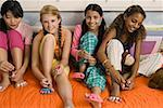 Four preteen girls painting toenails