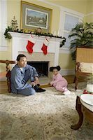 View of brother and sister sitting by fireplace decorated for Christmas, waiting for Santa Stock Photo - Premium Royalty-Freenull, Code: 638-01331200