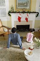 View of brother and sister sitting by fireplace decorated for Christmas, waiting for Santa Stock Photo - Premium Royalty-Freenull, Code: 638-01331820