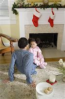 View of brother and sister sitting by fireplace decorated for Christmas, waiting for Santa Stock Photo - Premium Royalty-Freenull, Code: 638-01331909
